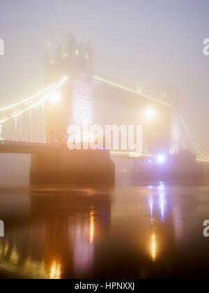 Tower Bridge beleuchtet in der Nacht im Nebel, London, UK - Stockfoto