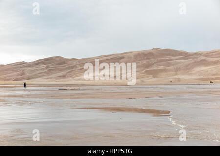 Menschen, die über einen Bach / Wasser zu den Dünen an der Great Sand Dunes National Park und Konserve, Colorado - Stockfoto
