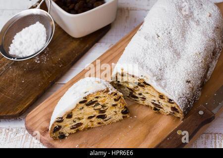 Pulverisierte Christstollen mit Cut-off-Slice auf Holzplatte, Zutaten, durch ein Sieb mit Puderzucker, Messer, rustikale - Stockfoto