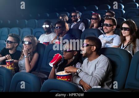 Unterhaltung-Snack. Junge afrikanische Mann isst Popcorn bei einem 3D Film seine Freundin ihr Getränk im Kino - Stockfoto