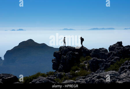 Touristen fotografieren einander auf Tafelberg mit dramatischen frühen Morgenlicht, Cape Town, Südafrika