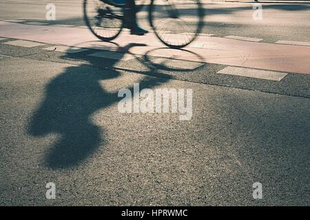 Silhouette der Radfahrer auf der Straße bei Sonnenaufgang - Stockfoto