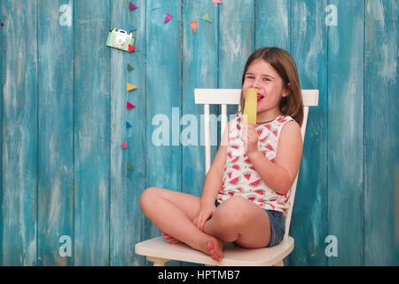 Glückliche kleine Mädchen sitzen auf Stuhl Essen Zitronen Eis am Stiel - Stockfoto