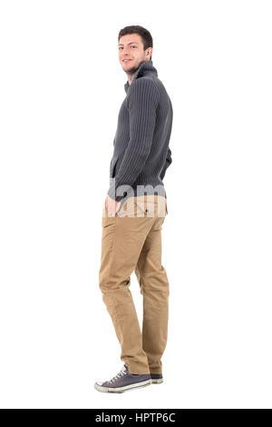 Rückansicht des jungen Mannes in Pullover mit Hände in den Taschen in die Kamera Lächeln. Ganzkörper-Länge-Porträt - Stockfoto