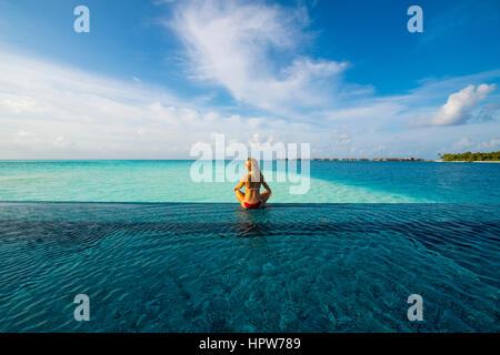 Maldives Rangali Island. Conrad Hilton Resort. Frau in einem Infinity-Pool auf das Meer. (MR) - Stockfoto