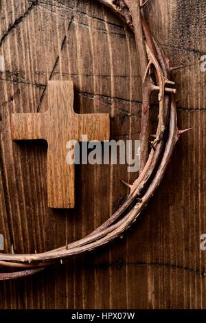 High-Angle Shot ein kleines Holzkreuz und eine Darstellung der Dornenkrone Jesu Christi auf eine Holzoberfläche - Stockfoto