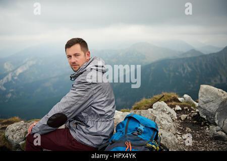 Porträt eines Mannes mit Wanderausrüstung sitzt auf einem Felsen bewundern Sie die Aussicht von oben auf einem Berg - Stockfoto
