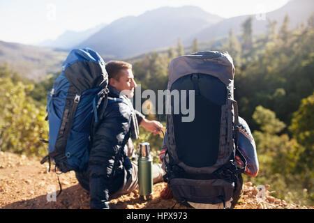 Junges Paar mit Rucksack wandern, eine Kaffee-Pause - Stockfoto
