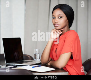 Attraktive junge Erwachsene Geschäftsfrau, Blick in die Kamera getrost beim Sitzen an ihrem Schreibtisch in ihrem - Stockfoto