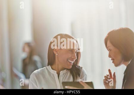 Lächelnde Unternehmerinnen im Gespräch, mit digital-Tablette - Stockfoto