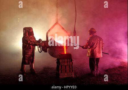 Gießt geschmolzenes Eisen in einem Stahlwerk Reenactment, metallurgische Arbeitnehmer mit Schöpflöffel Löffel, heiß, - Stockfoto