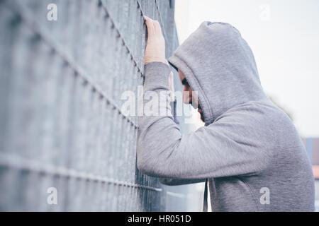 Einsamer Mann an einen Zaun gelehnt - Stockfoto