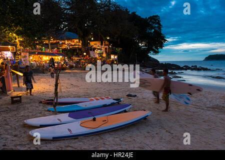 Surfer gehen mit Surfbretter bei Sonnenuntergang am Kata Beach, Phuket, Thailand - Stockfoto