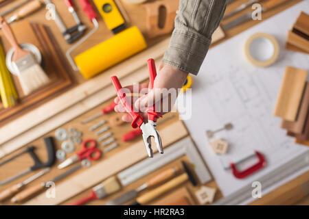 Männliche Hand Holding Zangen, Arbeitstisch mit Bau und die Reparatur Werkzeuge-Draufsicht, do it yourself und Renovierungs - Stockfoto