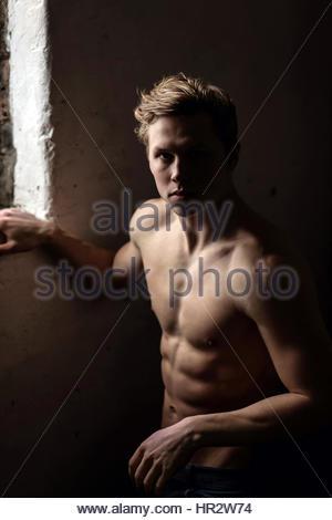 Nackter Oberkörper junger Mann in der Nähe eines Fensters - Stockfoto