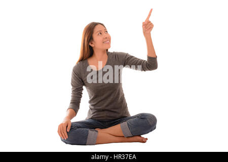 Lässige glückliche Frau sitzen und auf die oben auf weißem Hintergrund. Konzept und Idee Bild. - Stockfoto