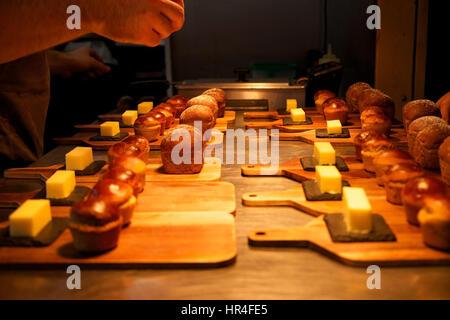 kleine Rollen von hausgemachtem Brot und Plätze der Butter auf Holzbrettern angelegt obenauf Silber Küche in einem - Stockfoto