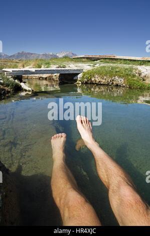 ein mans Beine einweichen in einer heißen Quelle in der östlichen Sierra in Kalifornien - Stockfoto