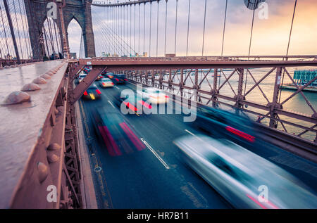 Verkehr auf der Brooklyn Bridge in New York City bei Sonnenuntergang - Stockfoto