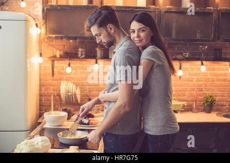 Junge schöne Paar in Küche. Familie mit zwei Zubereitung von Speisen. Frau, Blick in die Kamera und umarmen Mann - Stockfoto