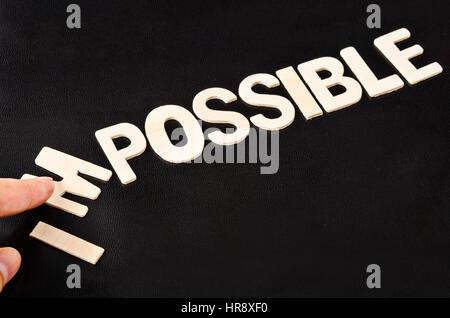 Hand des Mannes das Wort unmöglich von Holzbuchstaben, Herausnehmen der Buchstabe I M so es schriftlich möglich. - Stockfoto