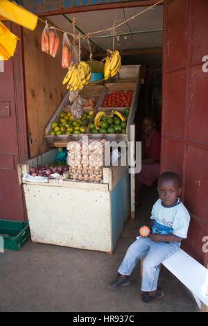 Junge Junge sitzt außerhalb Obststand, Slum Kibera in Nairobi, Kenia, Ostafrika - Stockfoto