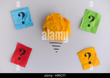 Auf der Suche nach neuen Ideen und Innovationen. Gelbe zerknittertes Papier Ball als eine Glühbirne und bunten Fragezeichen. - Stockfoto