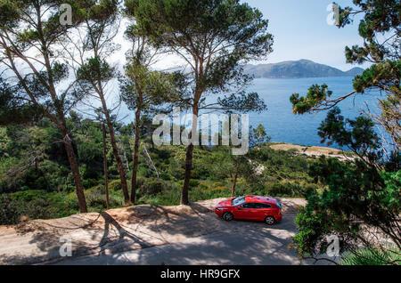 Alcudia, Mallorca, Spanien - 23. Mai 2016: Seascape des Mittelmeers mit einem roten Auto Volvo V40 Reisen auf dem - Stockfoto