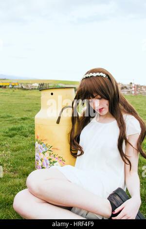Schöne und Brünette junge Frau ruht in einem grünen Feld - Stockfoto