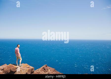 Jungen männlichen Reisenden auf Klippe stehend und weiten blauen Ozean während der Sommerferien auf Teneriffa - Stockfoto