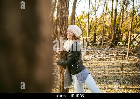 junge Frau geht zwischen den Bäumen am Ufer eines sonnigen Tages. gekleidet in einer schwarzen Lederjacke, blaue - Stockfoto