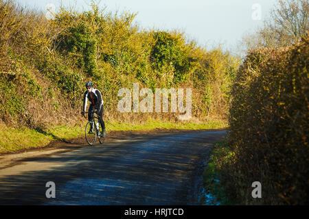 Ein Radsportler entlang einer Landstraße, an einem klaren sonnigen Wintertag. - Stockfoto