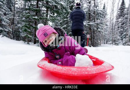 Ein kleines Mädchen (2 Jahre alt) wird von ihrer Mutter in einem Schlitten gezogen - Stockfoto