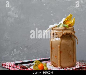 Schokolade Vegan Frühstück Smoothie mit Kiwi, Kokosnuss und Physalis in das Glas. Liebe für eine gesunde vegane - Stockfoto
