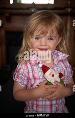 Kleines Mädchen hält einen Weihnachtsmann - Stockfoto