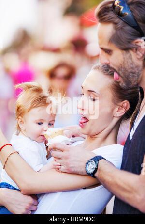 Mutter und Vater sind umarmt einen Babyjungen und fütterte ihn mit Eis im Freien. Kopieren Sie Raum. - Stockfoto
