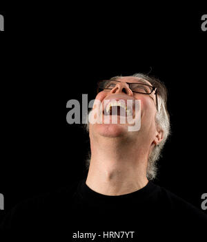 Kopfschuss Porträt eines älteren Mannes in seinen 50ern hautnah. Männchen tragen schwarzes T-shirt und auf schwarzem - Stockfoto