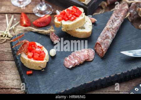 Scheiben Salami, Baguette und Tomaten auf dem Holzbrett. - Stockfoto