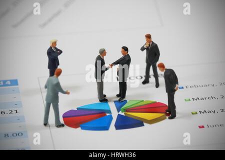 Draufsicht selektiven Fokus Miniatur Geschäftsmann Handshake auf bunten Kreis Diagrammhintergrund als Partnerschaft - Stockfoto