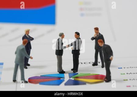 Selektiven Fokus Miniatur Geschäftsmann Handshake auf Kreis Diagrammhintergrund als Engagement und Investitionen - Stockfoto