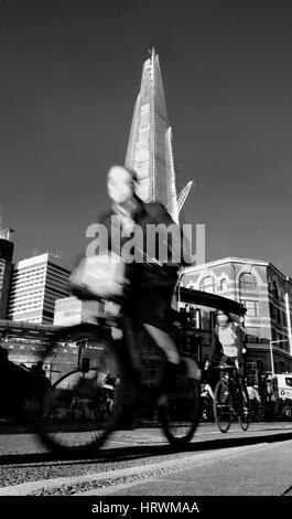 Ein Mann in einem Anzug Zyklen vorbei die Scherbe - Stockfoto