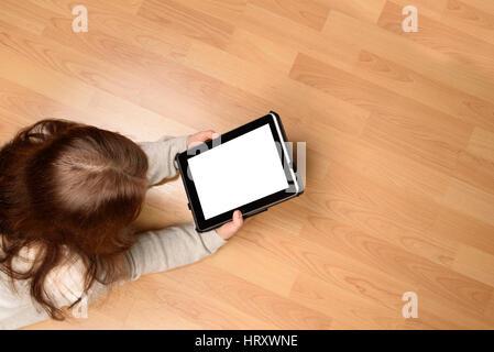 Draufsicht der jungen Frau liegt auf dem Boden mit einem tablet - Stockfoto