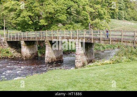 Stein-Fußgängerbrücke über der Flusses Wharfe in Bolton Abbey in den Yorkshire Dales. Die Brücke ist mit lokalem - Stockfoto