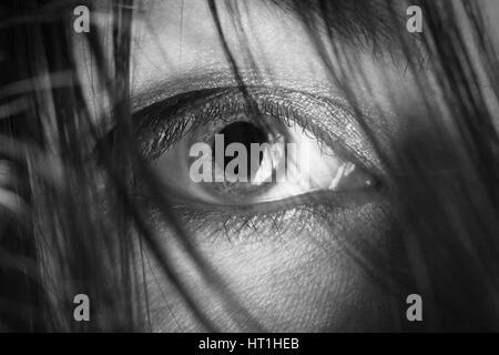 weibliche Auge, Blick in die Kamera durch schwarzes Haar Closeup monochromes Bild - Stockfoto