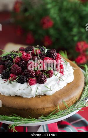 Cranberry und Himbeer Kuchen auf roten Holztisch, Mäusedorn Blumen im Hintergrund. - Stockfoto