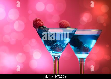 Bunte Cocktails, garniert mit Beeren, Hintergrund mit Lichteffekten - Stockfoto