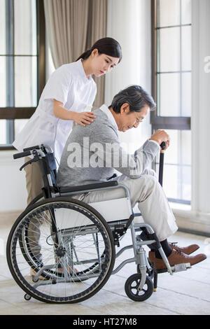 Pflegehelferin kümmert sich der ältere Mann im Rollstuhl - Stockfoto