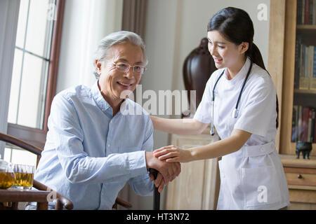 Pflegehelferin kümmert sich um ältere Mann - Stockfoto