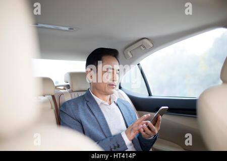 Geschäftsmann mit Smartphone im Auto - Stockfoto