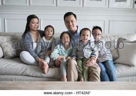 Porträt, Lächeln junge Familie auf dem Sofa im Wohnzimmer - Stockfoto